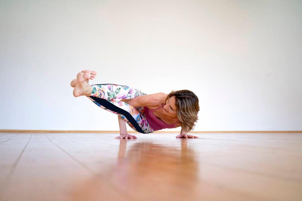 Frau praktiziert die Yoga-Übung seitliche Krähe