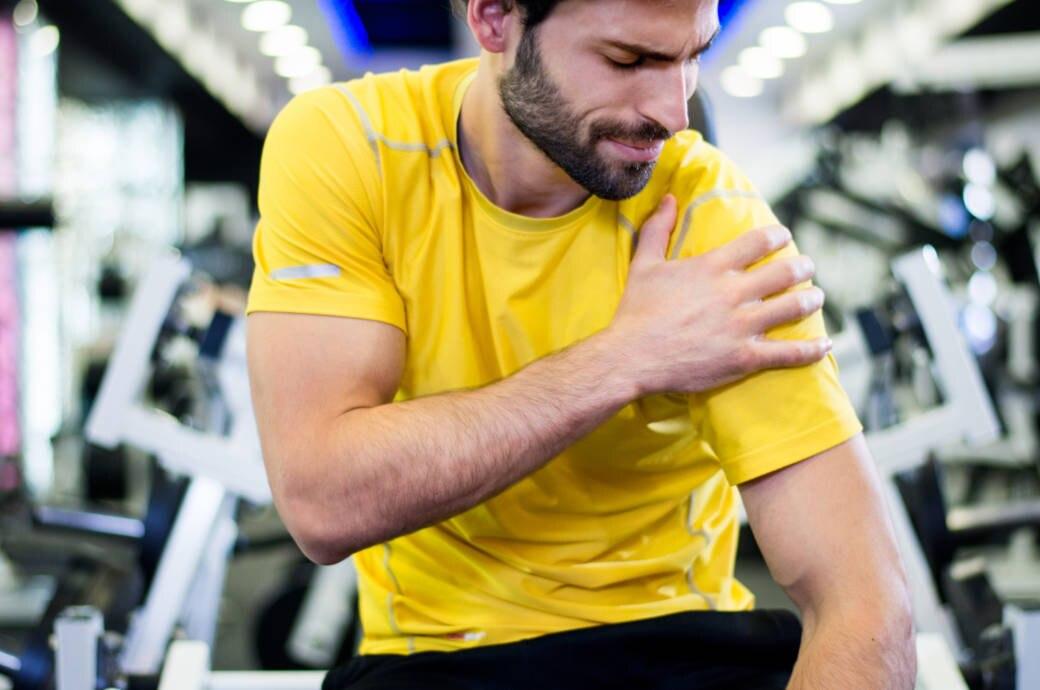 Ein Mann hält sich im Fitnessstudio vor Schmerzen die Schulter