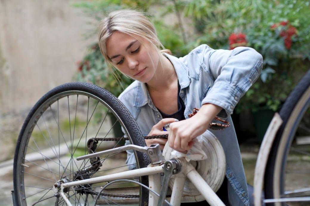 Eine junge Frau reinigt ihr Fahrrad