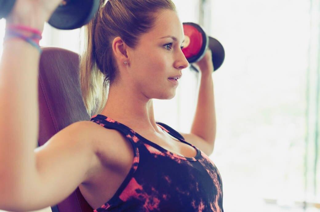 Frau macht konzentriert Übungen im Fitnessstudio