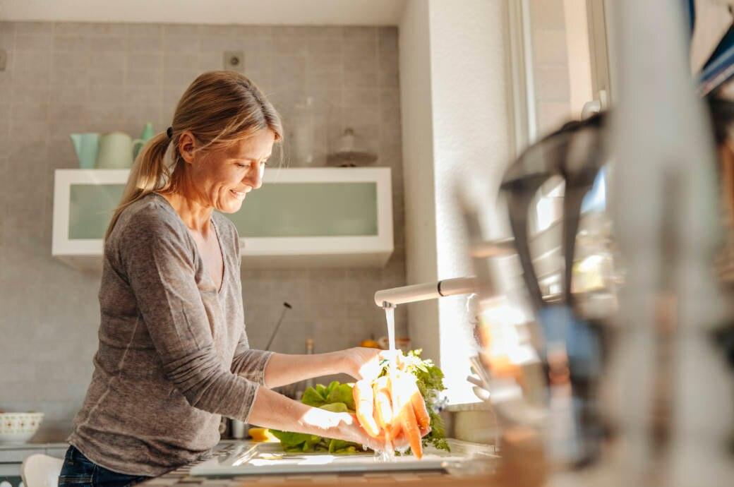 Ein Frau mittleren Alters wäscht Karotten in ihrer Küche