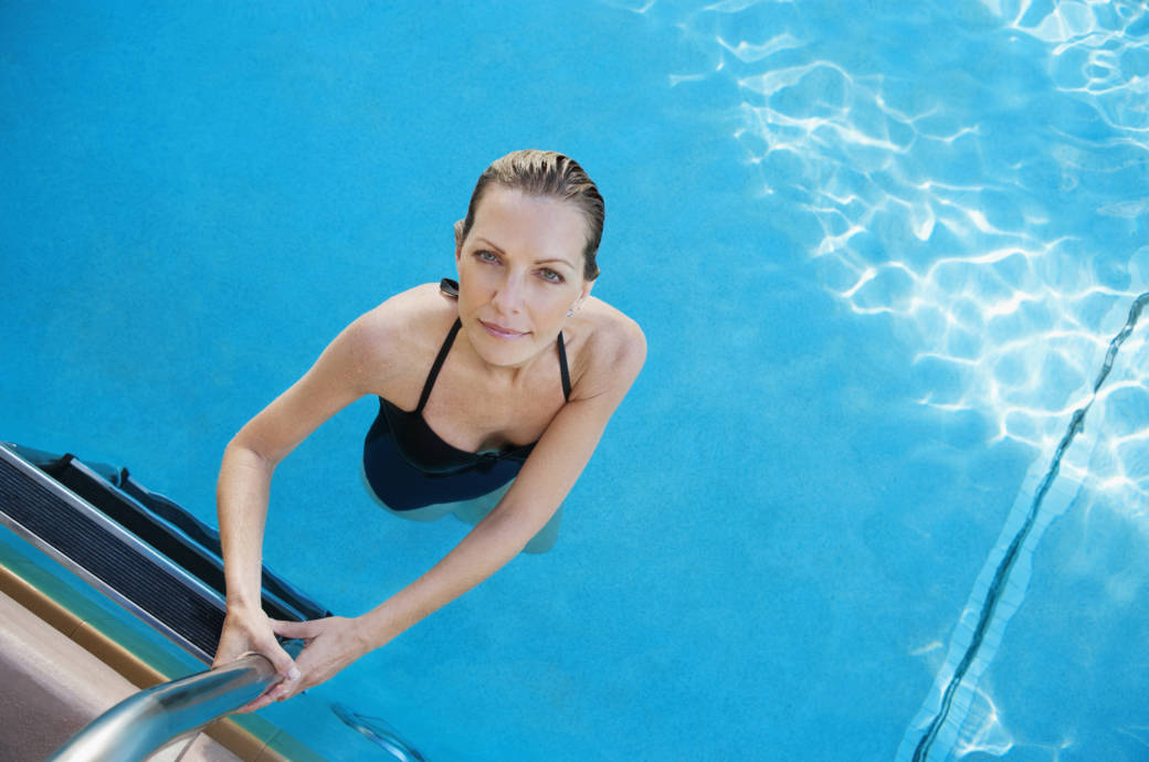 Eine Frau steigt in einen Swimmingpool