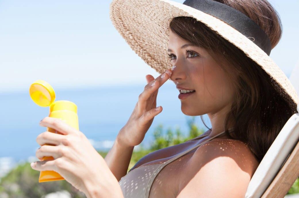 Eine Frau mit Hut und Sonnencreme auf einer Liege