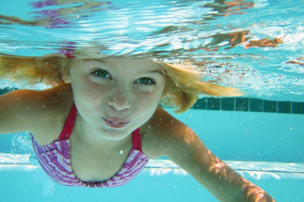 Ein Kind taucht in einem Schwimmbecken