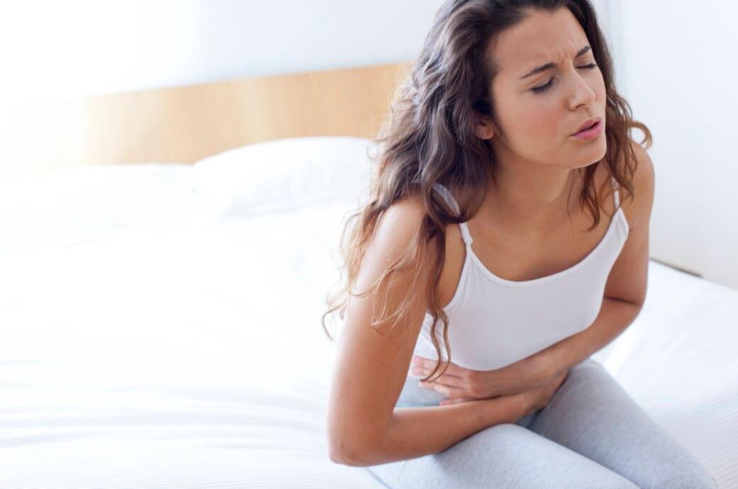 Frau auf dem Bett mit Blähungen