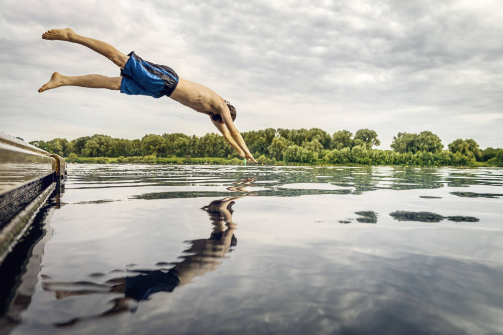 Ein Mann springt von einem Steg in einen See