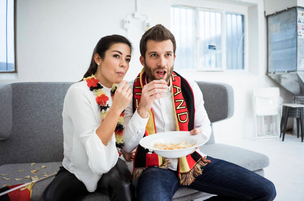 Ein Pärchen isst Chips und schaut Fußball