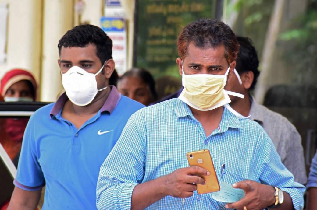 Zwei Männer schützen sich mit Gesichtsmasken in Indien vor dem Nipah-Virus