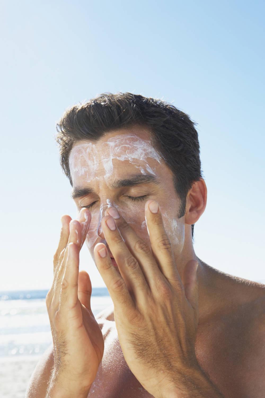 Mann reibt sich mit Sonnenschutz ein