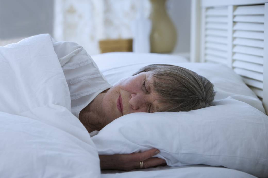 Eine ältere Frau liegt im Bett