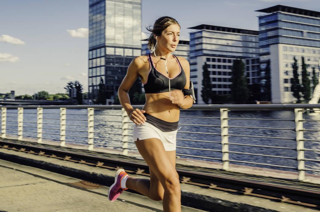 Eine Frau läuft im Sommer an einem Fluss entlang