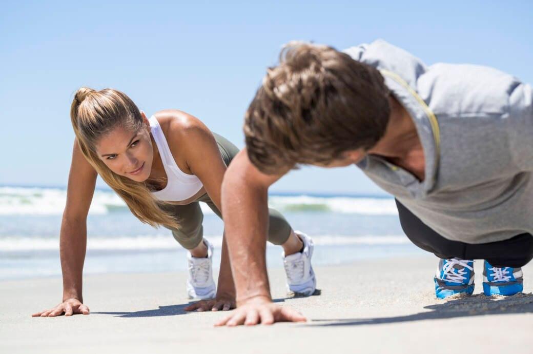 Ein Pärchen trainiert am Strand