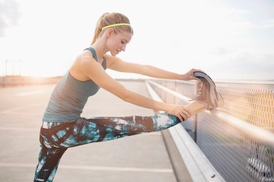 Eine junge Frau dehnt sich nach dem Laufen