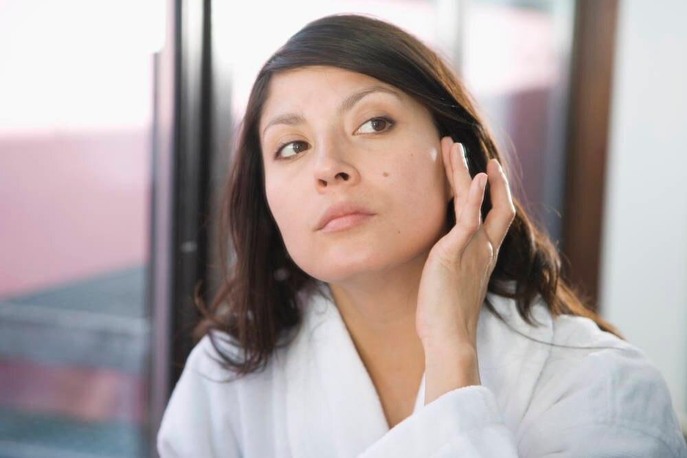 Frau betrachtet ihr Muttermal