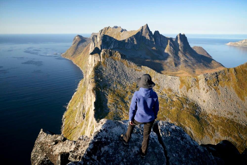 Mann steht am Abgrund und schaut sich Bergpanorama an