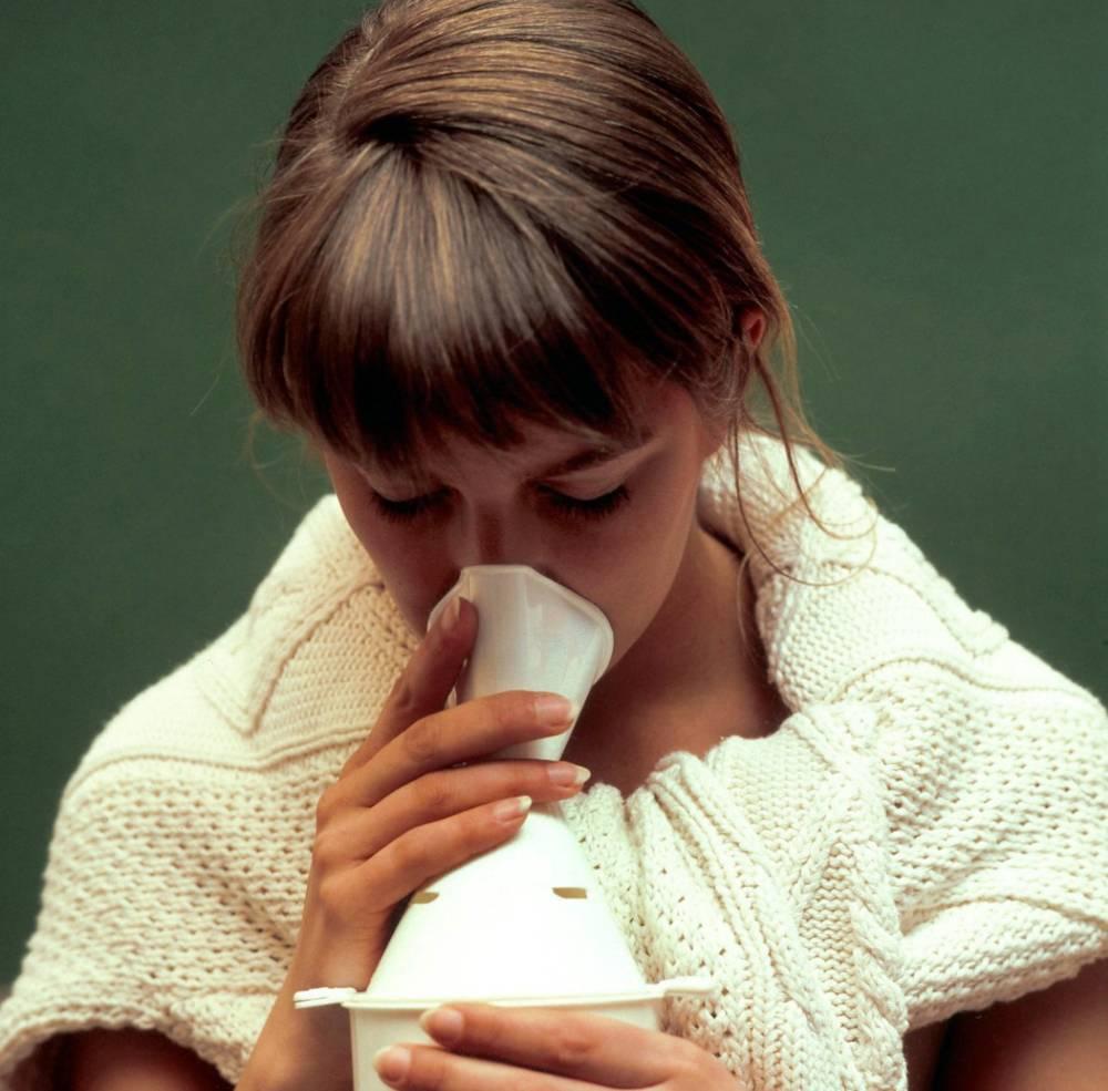 Eine junge Frau benutzt ein Inhalationsgerät