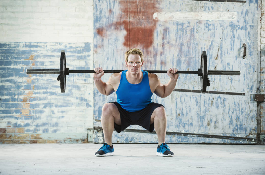 Mann macht Kniebeuge mit Gewichten
