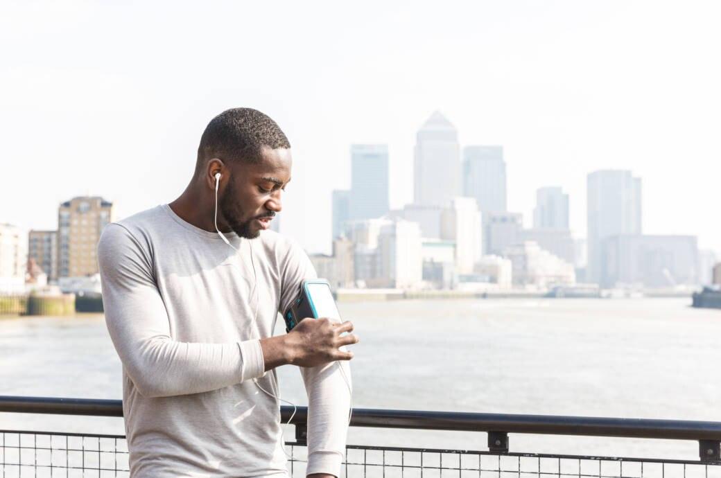 Ein Mann stellt an seinem Handy etwas ein bevor er losjoggt