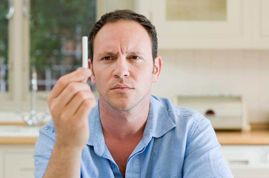 Mann hält Zigarette