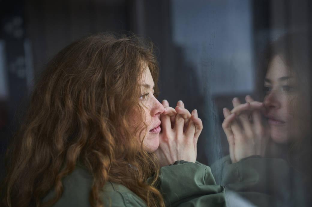 Eine Frau guckt traurig aus einem Fenster