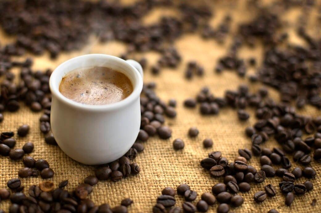 Eine Tasse Kaffee auf einem Tisch mit Kaffeebohnen