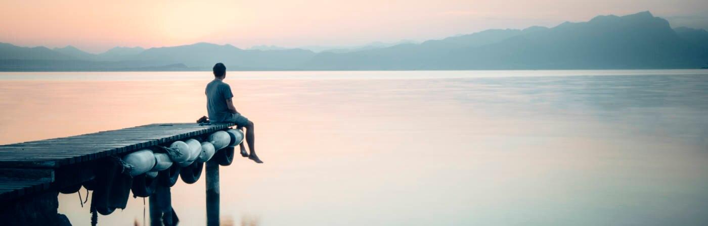 Mann sitzt an stillem See und schaut in die Ferne