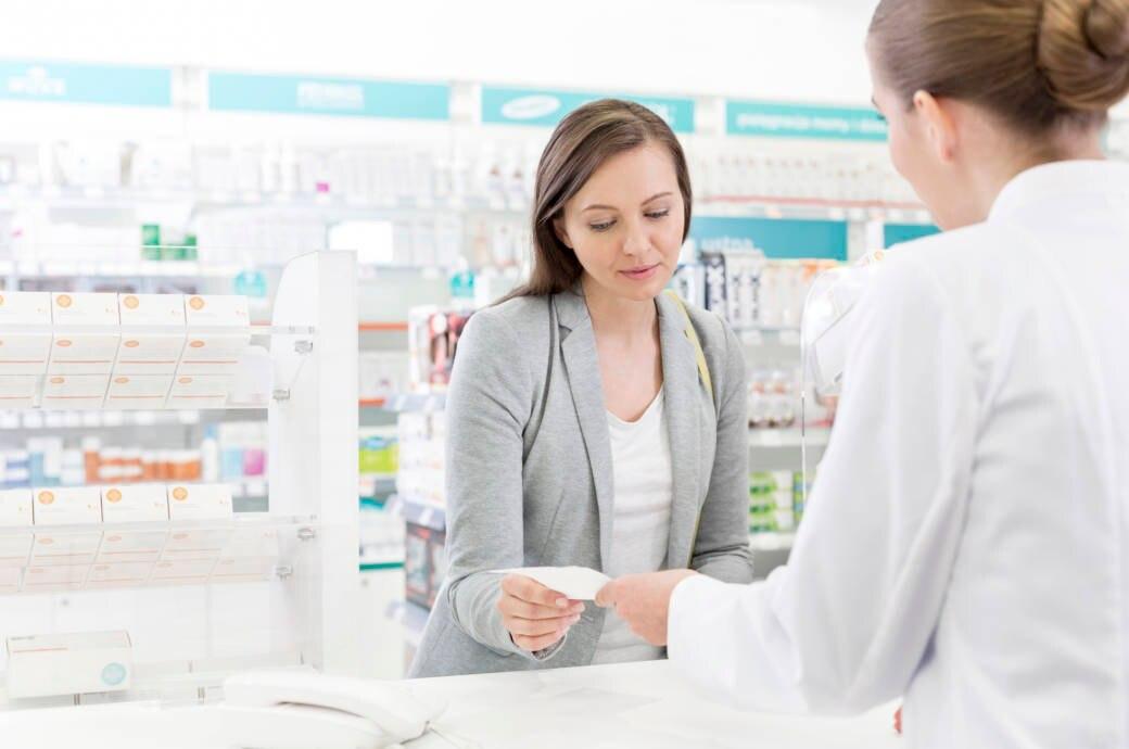 Ein Patient gibt sein Rezept einer Apothekerin