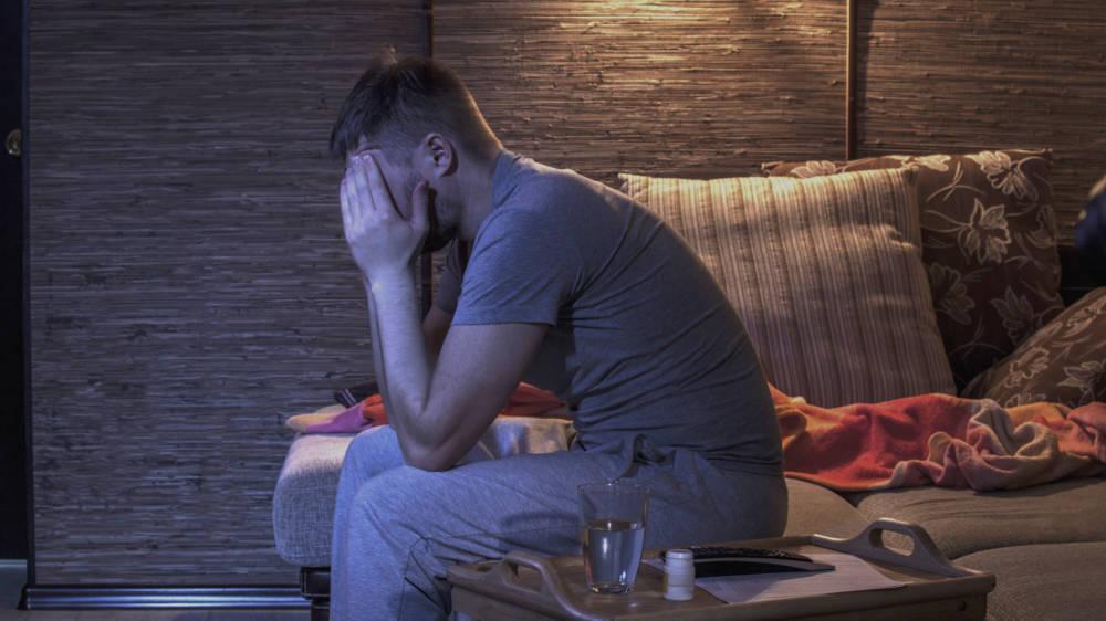 Mann auf dem Bett mit Kopfschmerzen
