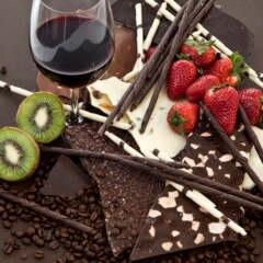 Schokolade und Früchte auf einem Teller, dazu ein Glas Rotwein