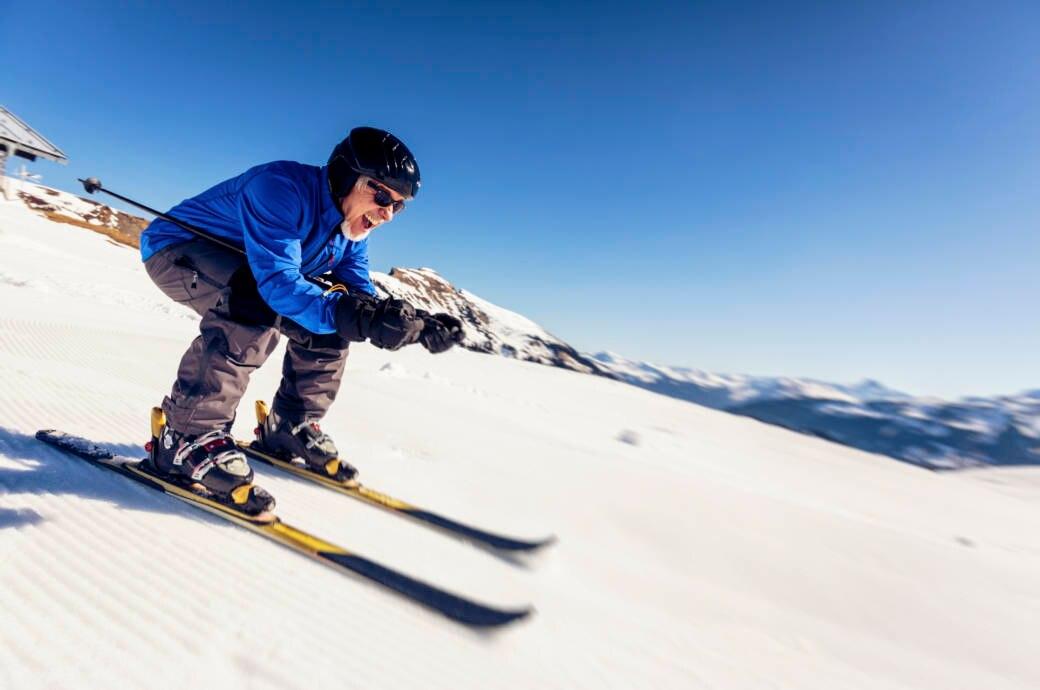 Ein älterer Mann hat Spaß beim Skifahren