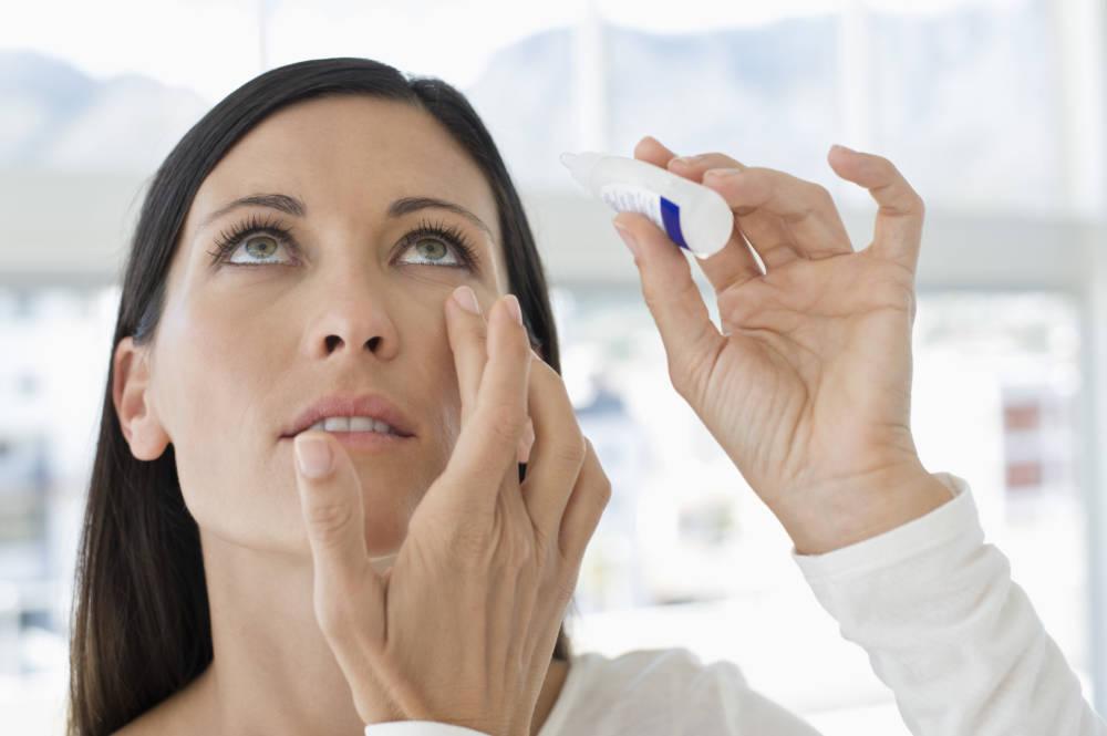 Frau benutzt Augentropfen