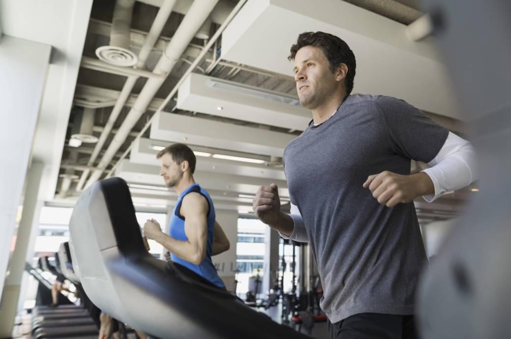 Ein junger Mann joggt auf einem Laufband in einem Fitnessstudio