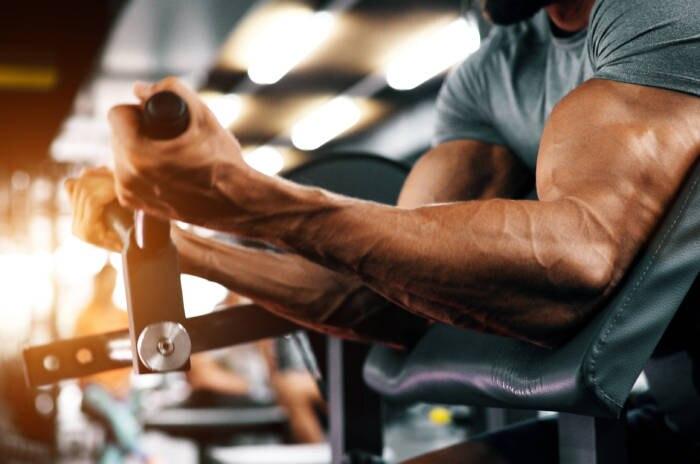 Muscular bodybuilder guy doing exercises
