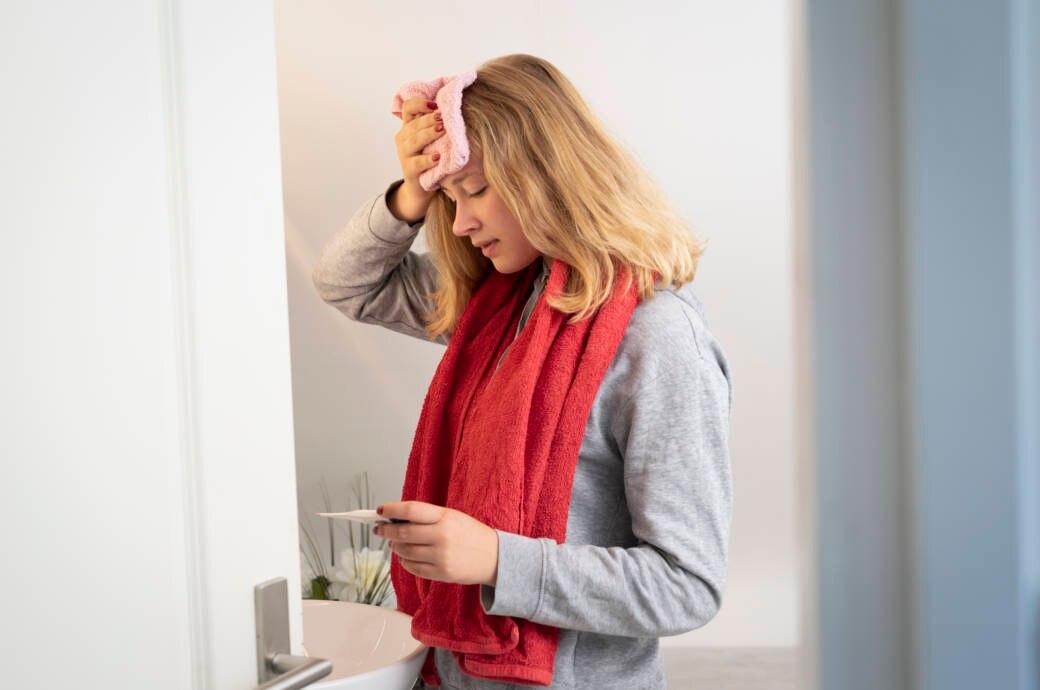 Eine junge Frau schaut auf ihr Fieberthermometer