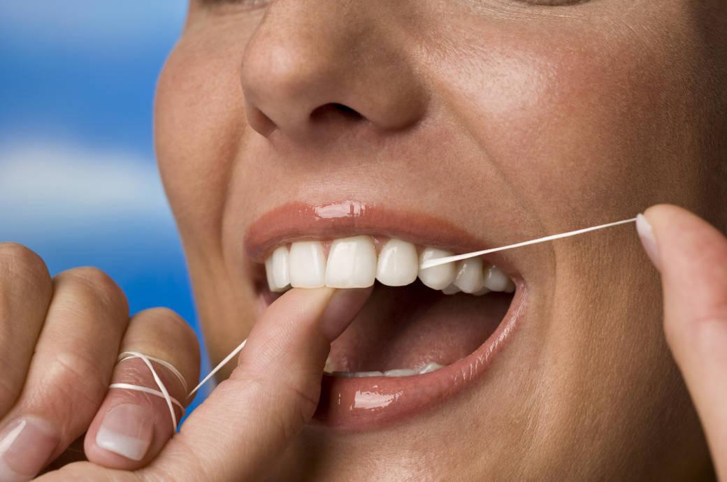 Frau reinigt ihre Zähne mit Zahnseide