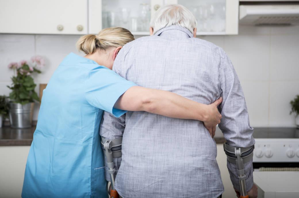 Helferin mit Parkinson-Patient