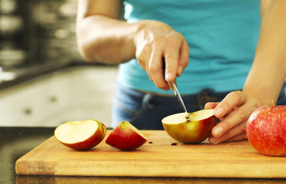 Frau schneidet Äpfel