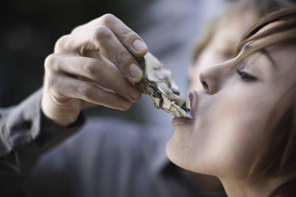 Frau schlürft eine Auster