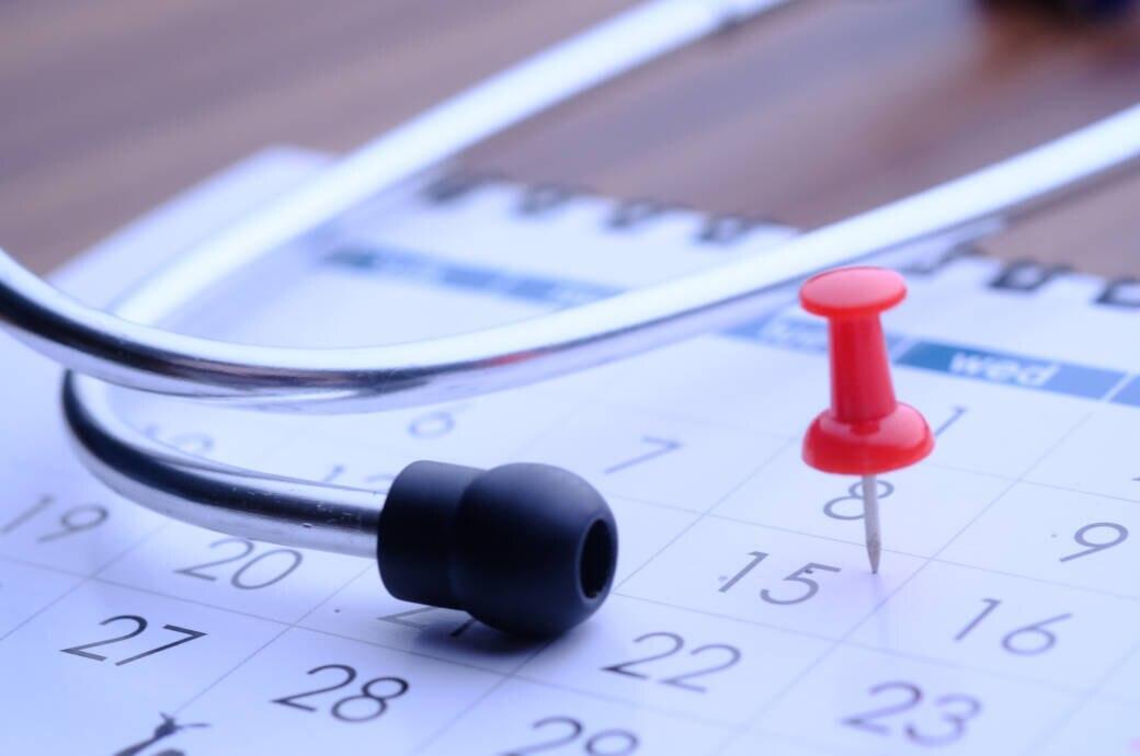 Ein Kalender und ein Stethoskop auf einem Tisch