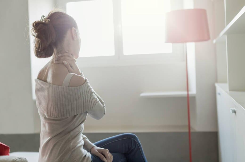 Eine junge Frau hält sich den Nacken