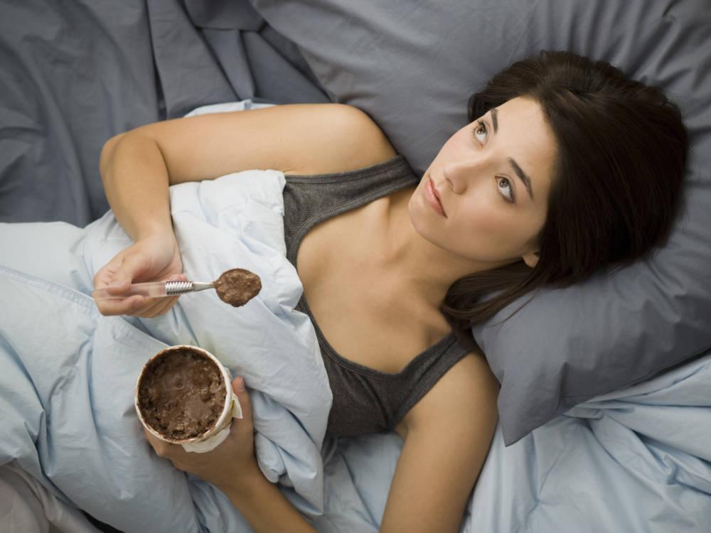 Frau liegt mit Schokolade im Bett