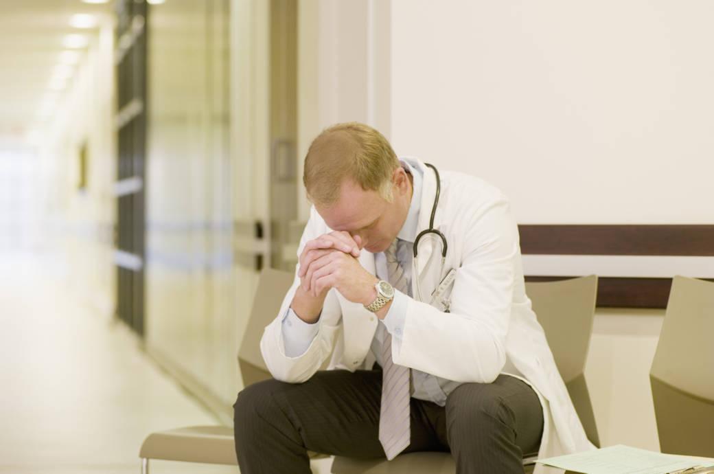 Ein nachdenklicher Arzt sitzt auf einem Stuhl