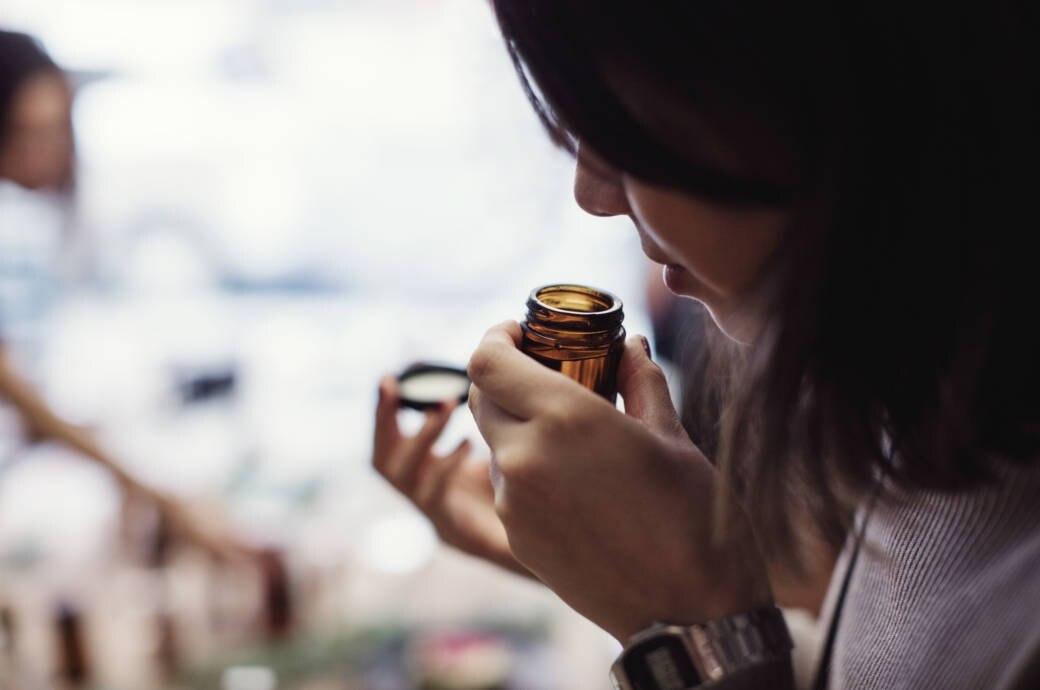 Frau riecht an einem Behälter
