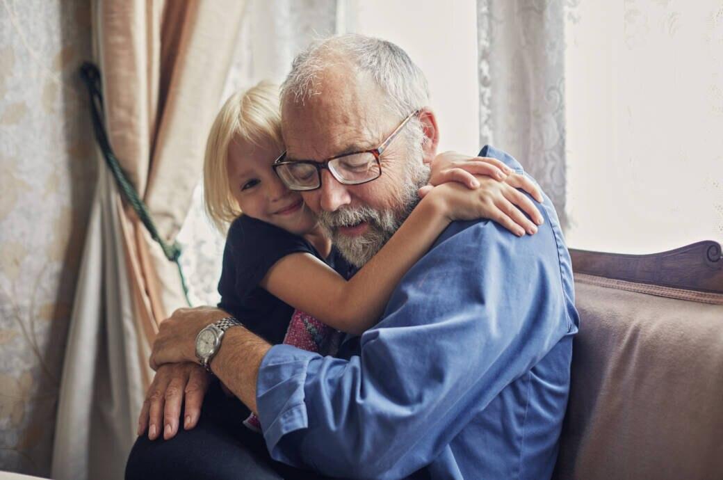 Ein kleines Mädchen umarmt ihren Großvater