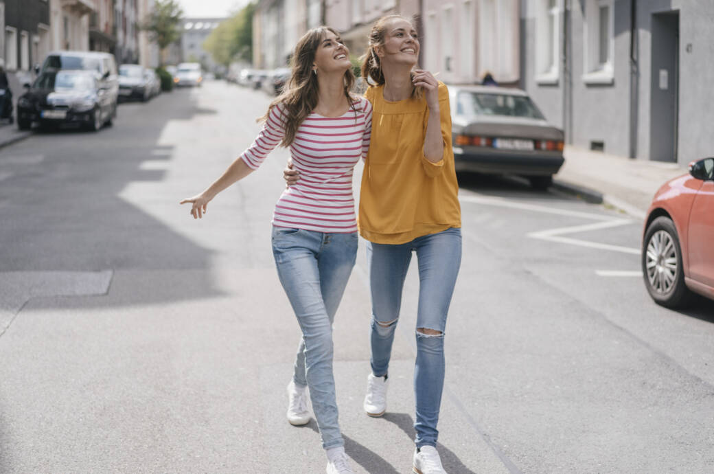 Zwei junge Frauen gehen Arm in Arm spazieren