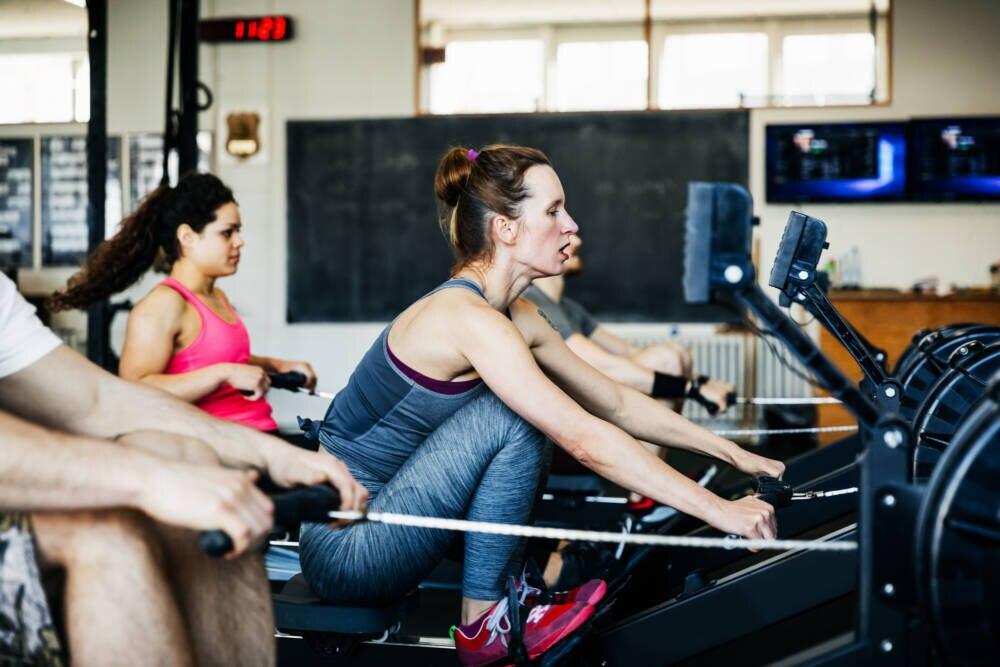 Frauen trainieren an Rudermaschinen