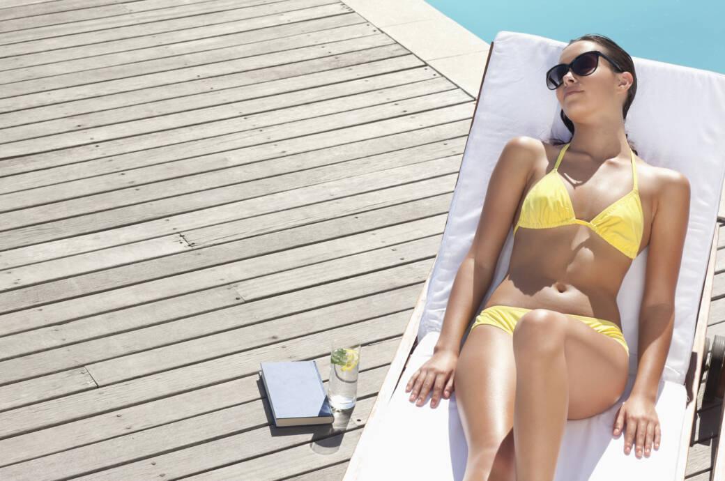 Eine junge Frau chillt im Urlaub am Pool
