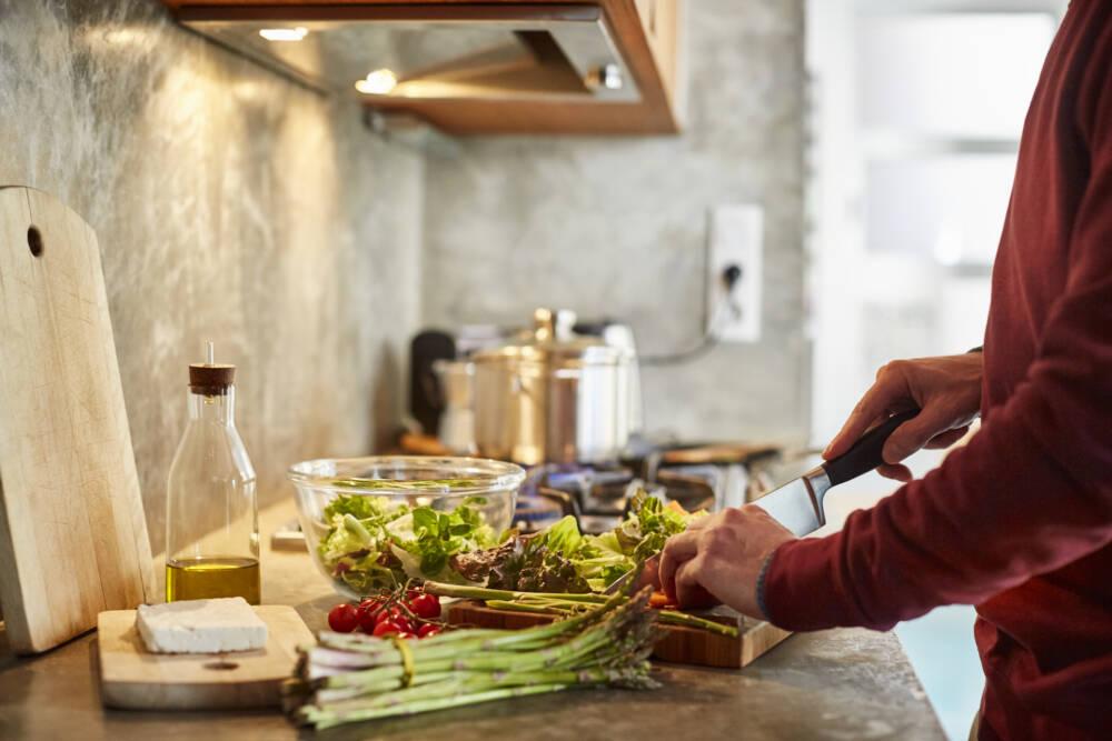 Mann bereitet sich Gemüse zu