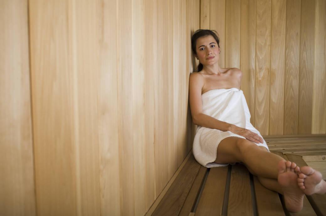 Schöne junge Frau sitzt in der Sauna