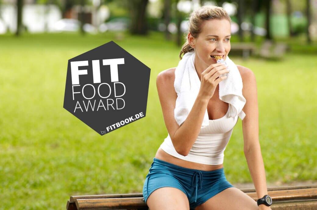 Ein Frau sitzt nach dem Sport auf einer Parkbank und isst einen Proteinriegel